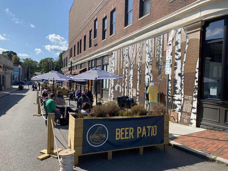 """A narrow patio, with blue umbrella-bedecked tables, sits alongside a brick building that is painted with a large mural of elm trees. A sign at the front of the patio reads """"beer patio."""""""