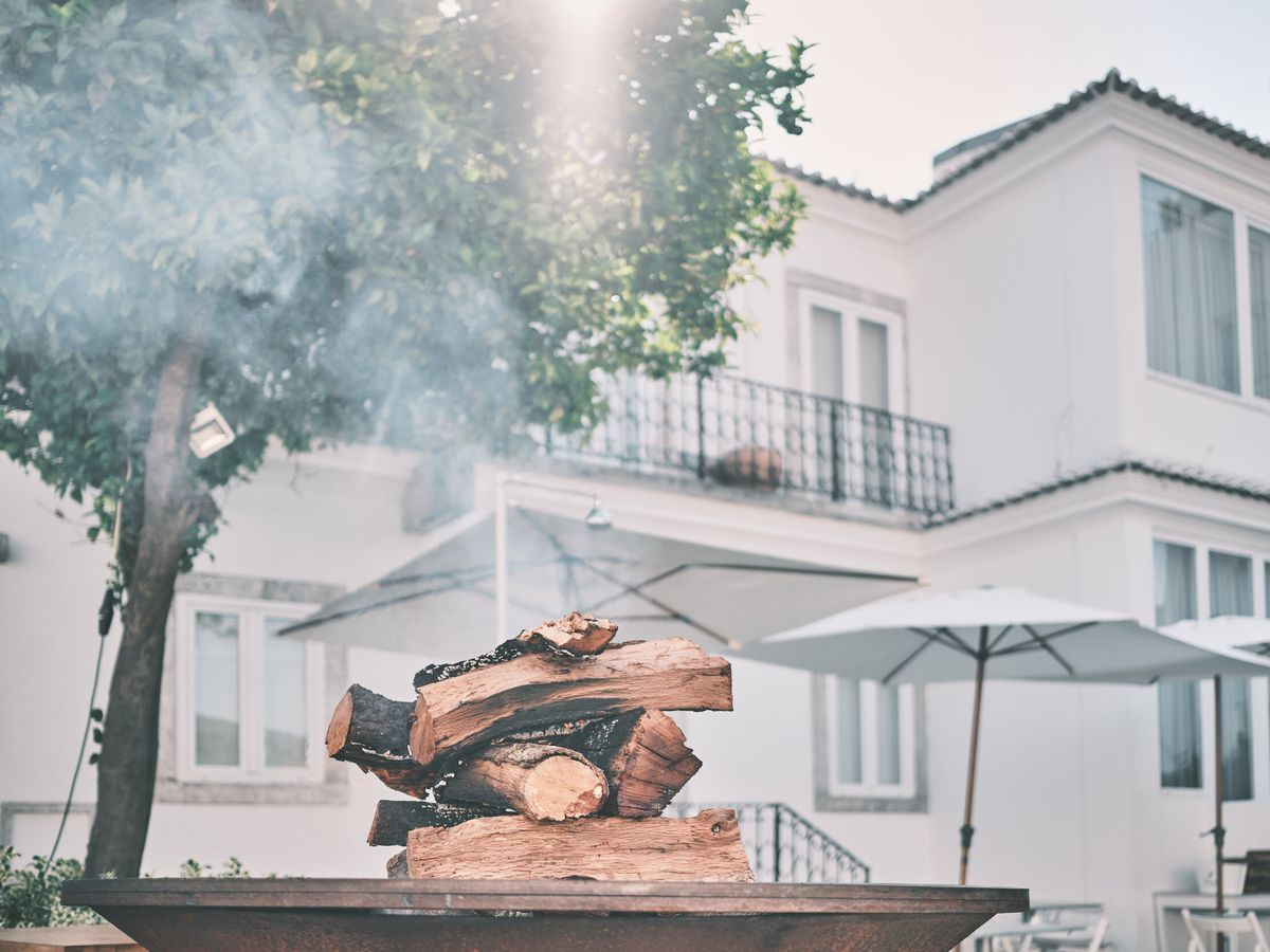 A stack of wood on a grill, in front of a building facade and large tree