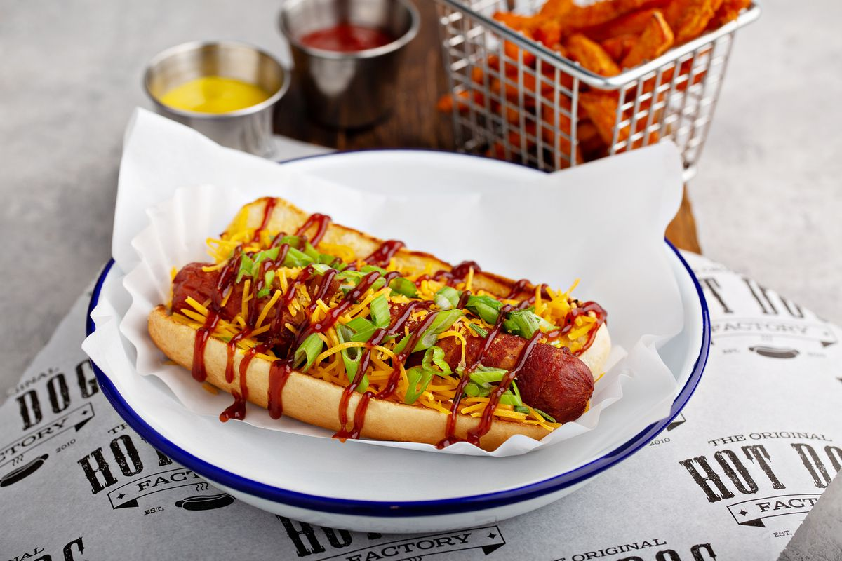 The Memphis bacon-wrapped hot dog sitting in a white bowl with blue rim drizzled with BBQ sauce, mustard, and shredded cheese. A basket of sweet potato fries and tins of ketchup and mustard in the background