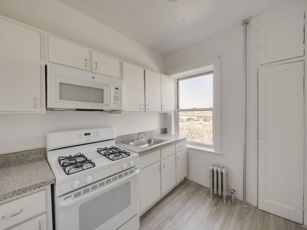 A kitchen with white cabinetry, a window, and white walls.