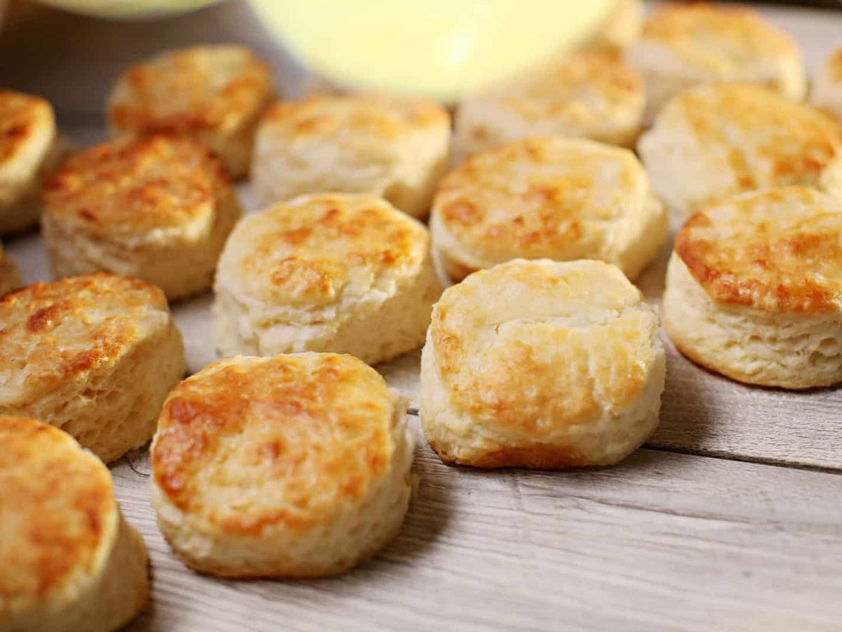 A board full of biscuits with a well of butter