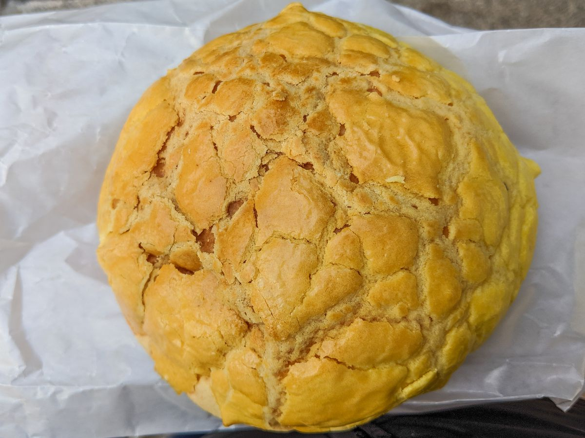 A big, round, yellow pineapple bun with a crackly top sits on a white paper bag