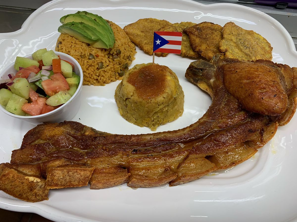 A giant fried pork chop on a plate with a side of rice and tostones and a mofongo topped with a tiny Puerto Rican flag