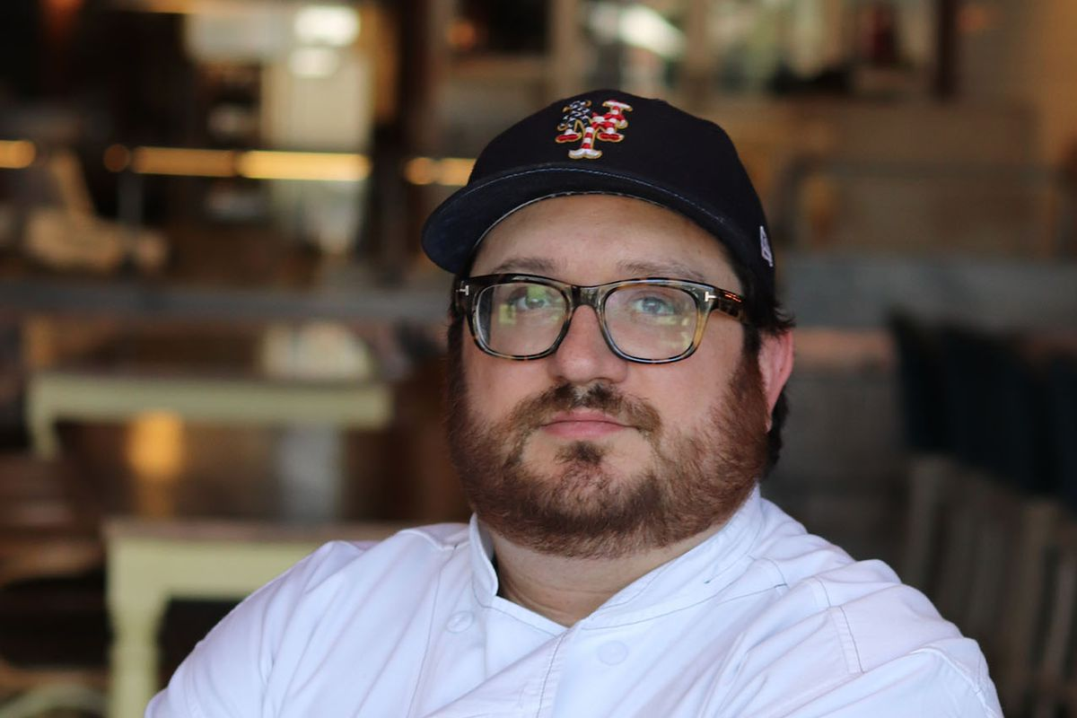 A chef poses with a hat and his arms crossed