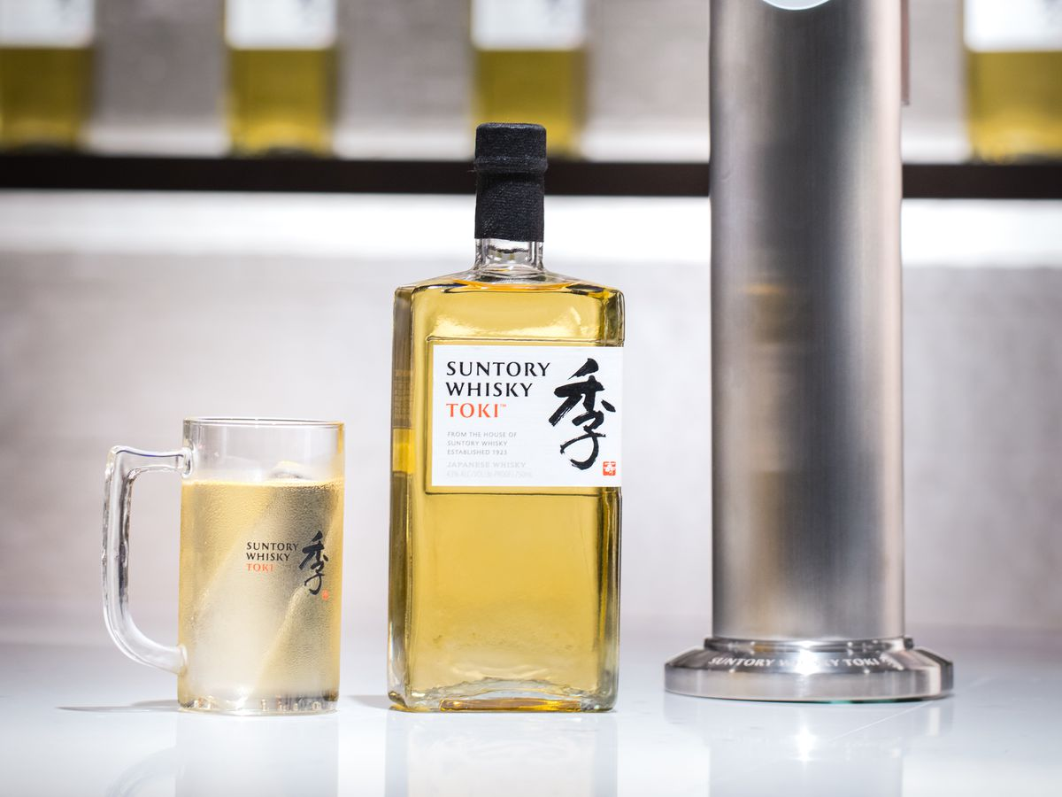 A bottle of Suntory Toki whisky sits on a bar between the tall silver spout of the highball machine and a fizzy toki highball
