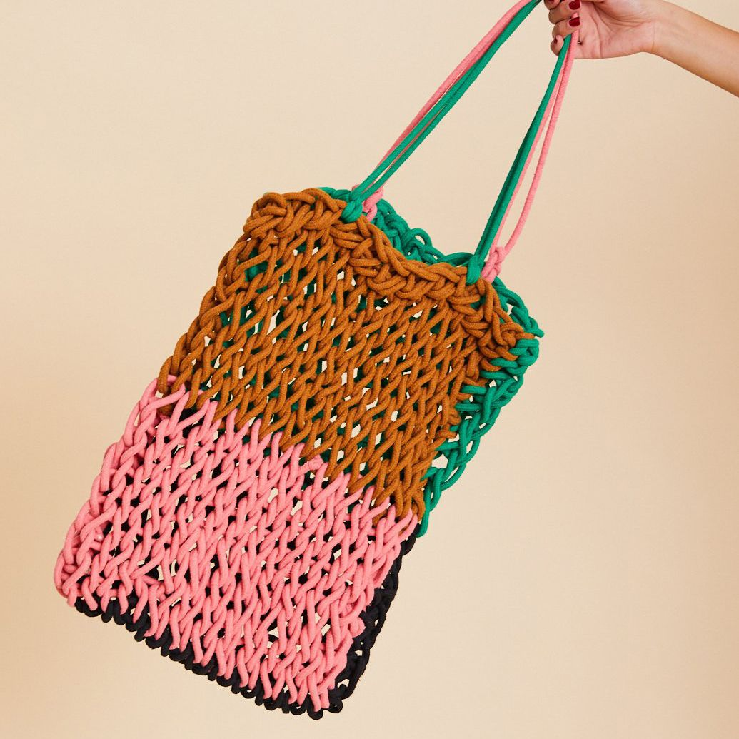 A hand holds up a tote made of pink, dark red, and green yarn.