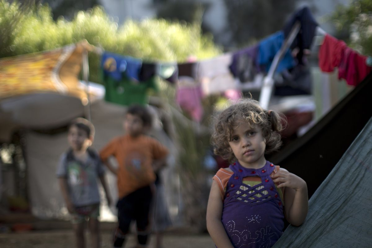 A displaced Palestinian girl stands next to a makeshift tent at the al-Shifa hospital in Gaza City where many Palestinians have have taken refuge after fleeing attacks in the Shejaiya neighbourhood of the city.
