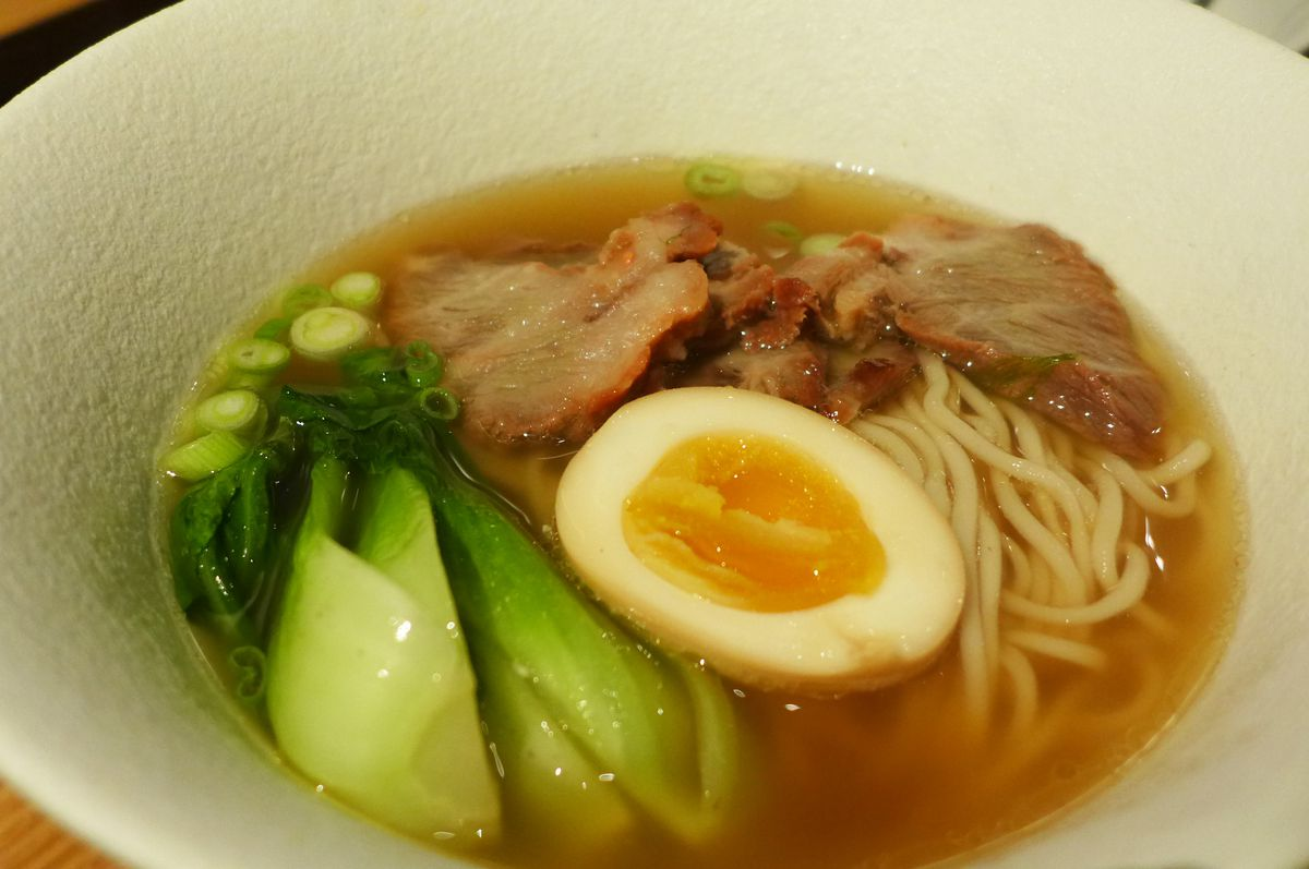 A bowl of noodle soup also has green bok choy and a yellow yolked hard cooked egg...