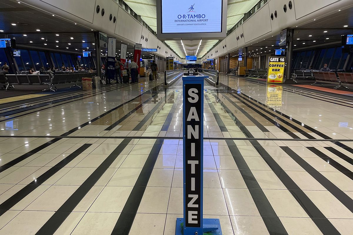 In this Monday Dec. 21 2020 file photo a hand sanitizing pump stands in the middle of a near empty departure terminal as few passengers board and Air France flight to Paris at Johannesburg's OR Tambo airport.