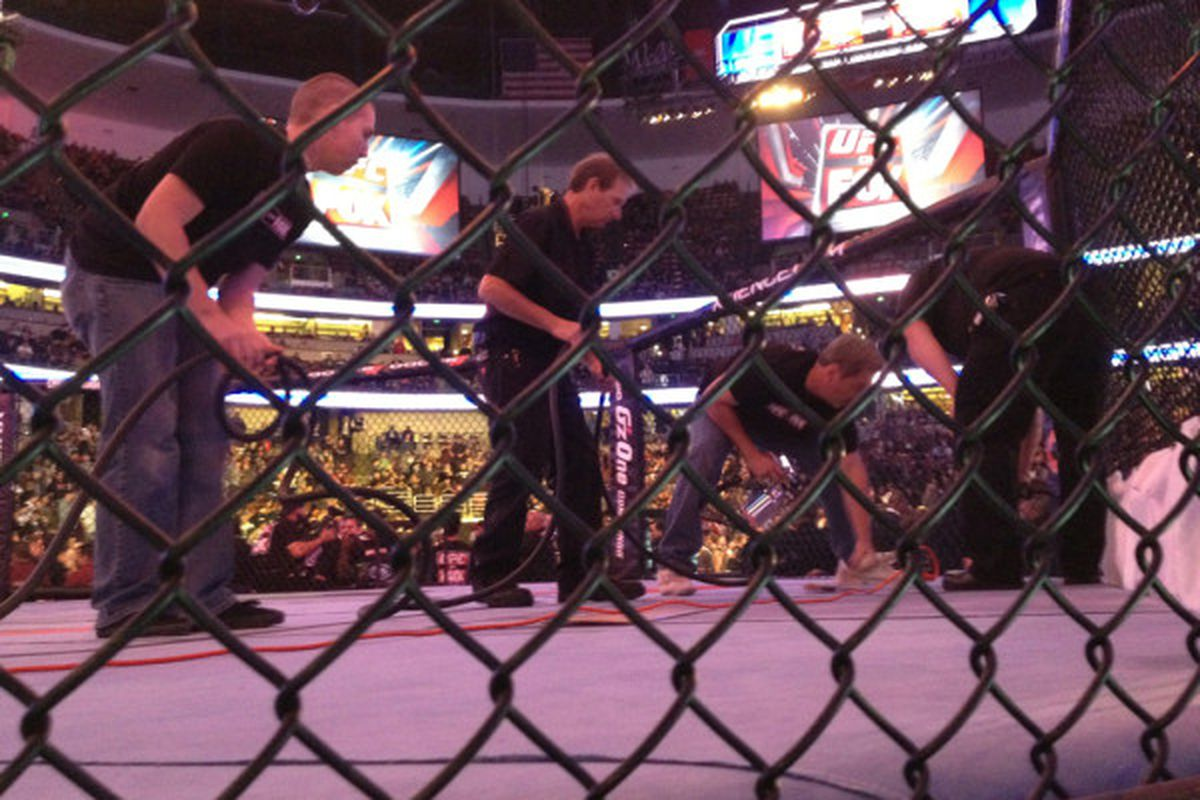 """Production crew paints over blood in the UFC Octagon before the heavyweight championship bout at UFC on Fox in Anaheim, California's Honda Center. Photo by <a href=""""http://twitter.com/#!/allelbows/statuses/135538751551180800""""> Esther Lin.</a>"""