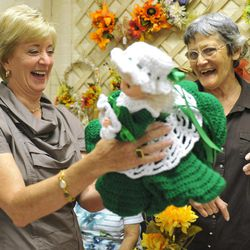 In this Tuesday, Sept. 18, 2012 photo, Republican candidate for U.S. Senate Linda McMahon, left, looks at a doll made by Bernice Niro during a visit to the Naugatuck Senior Center in Naugatuck, Conn. Wealthy former pro wrestling executive McMahon is shifting her image from groin-kicking CEO to grandmother in her second bid for a Senate seat from Connecticut. Polls show the strategy seems to be working against three-term Democratic congressman Chris Murphy.