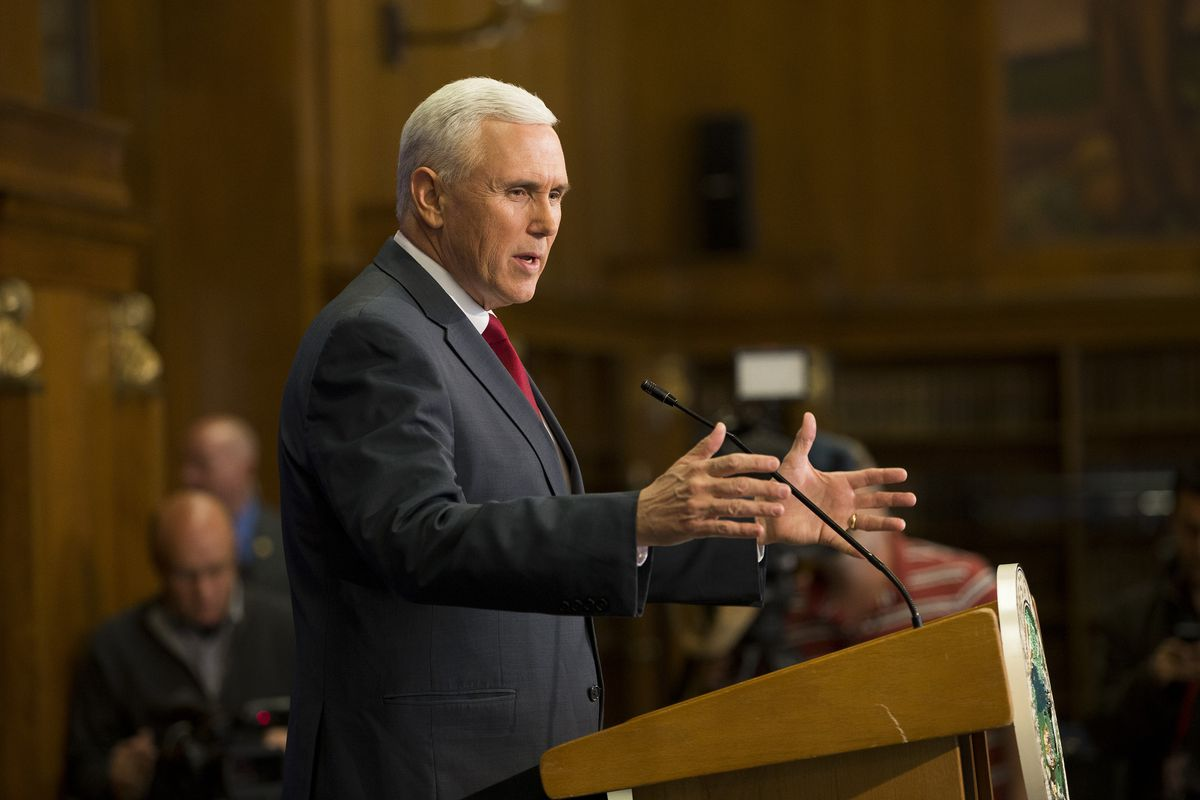 Vice President Mike Pence, in a dark gray suit and red tie, gestures with both hands at a podium while speaking into a microphone.