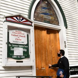 The Rev. Salvatore Sapienza locks up the Douglas Congregational United Church of Christ in the village of Douglas, Mich.,on Tuesday Oct. 13, 2020. As part of the Our Faith Our Vote 2020 initiative, volunteers at the church will drive voters with their completed mail-in ballots to the county clerk's office to drop them off in person. The drivers and voters will be masked and separated in vehicles to minimize any COVID-19 risk.