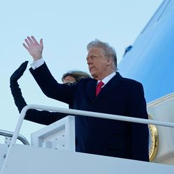 US President Donald Trump and First Lady Melania Trump wave as they board Air Force One at Joint Base Andrews in Maryland on January 20, 2021. - President Trump and the First Lady travel to his Mar-a-Lago golf club residence in Palm Beach, Florida, and will not attend the inauguration for President-elect Joe Biden.