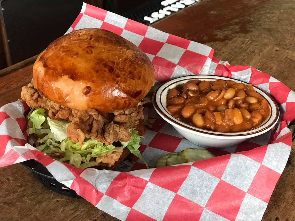 A crispy fried sandwich with shredded lettuce in a basket with a side of pinto beans