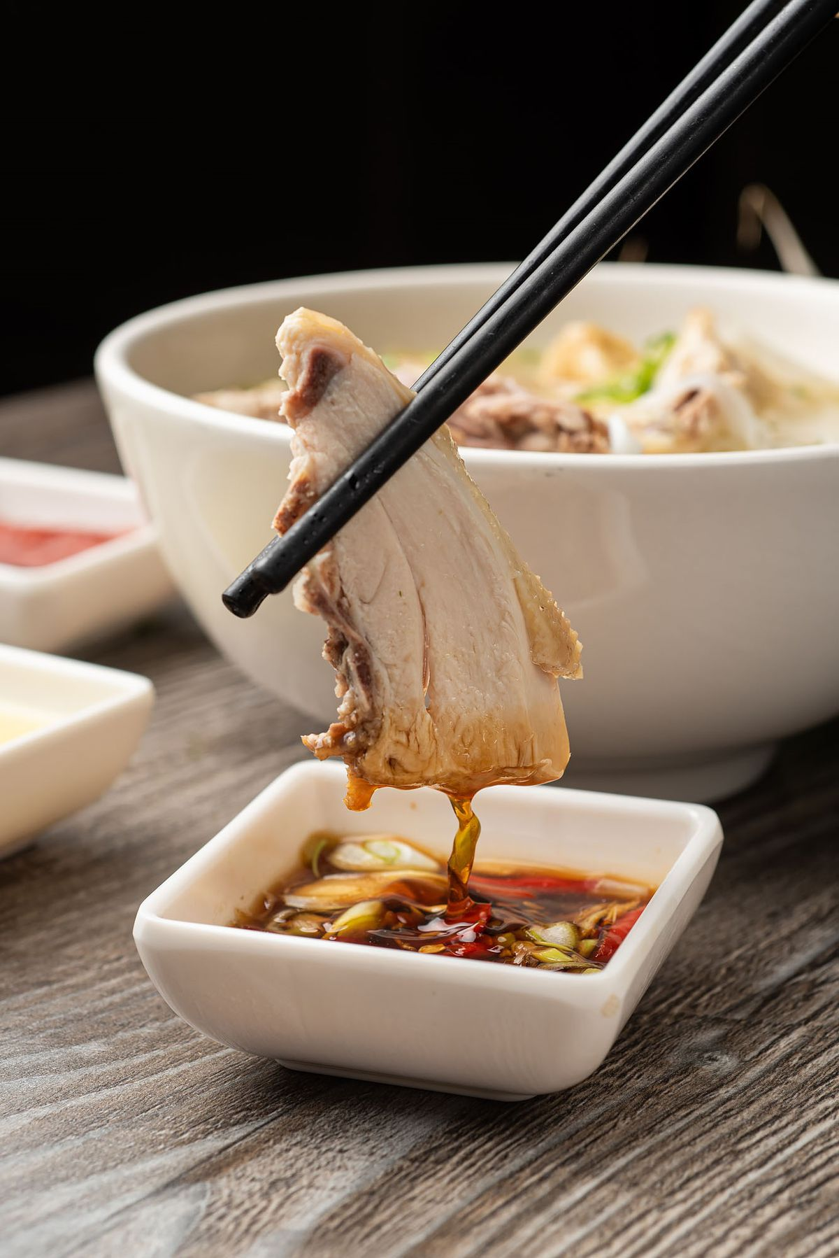 Dipping chicken into sauce at Pho Ga District.