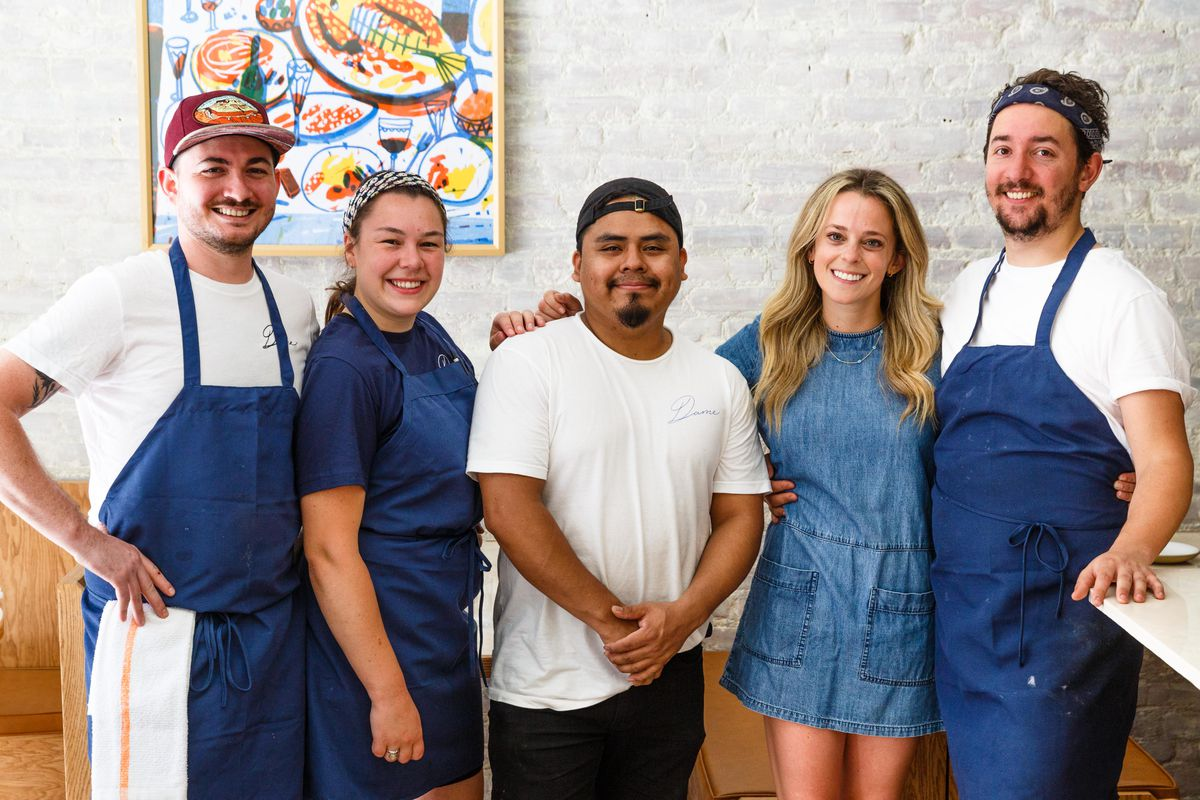A portrait photo of five smiling people lined up against a white brick wall with artwork in the background