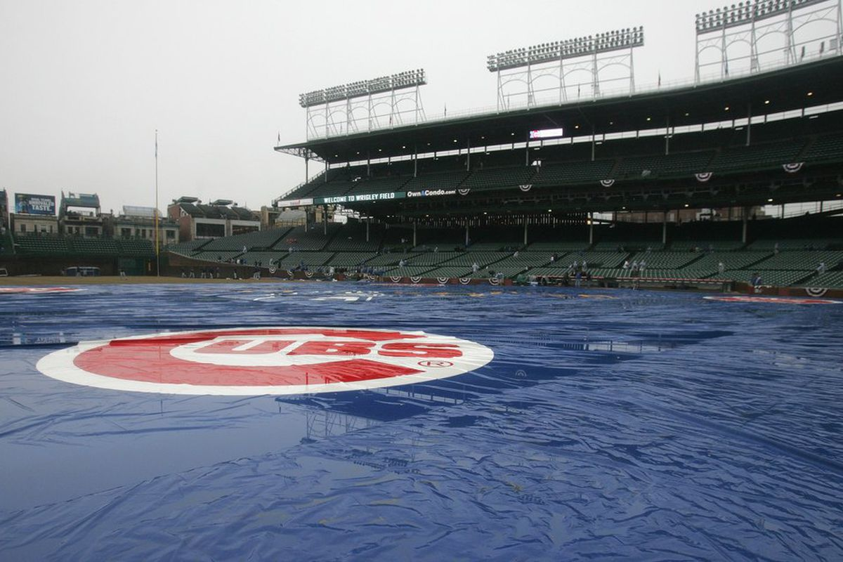 Water stands on the tarp during a rain delay between the Chicago Cubs and the Milwaukee Brewers at Wrigley Field in Chicago, Illinois. (Photo by Jonathan Daniel/Getty Images)
