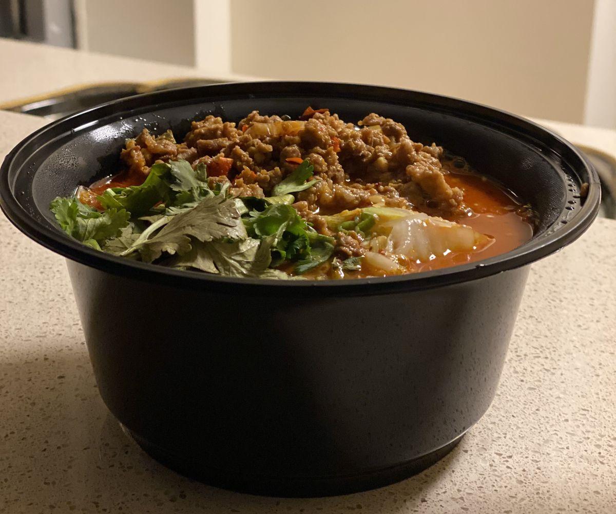 Ground pork and cilantro sit above a crimson broth in a black plastic bowl