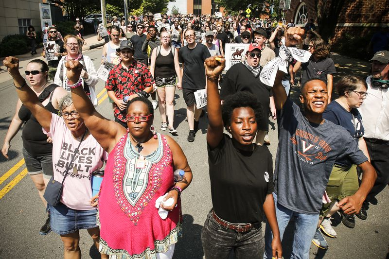 Demonstrators against racism march along city streets as they mark the anniversary of last year's Unite the Right rally in Charlottesville, VA.