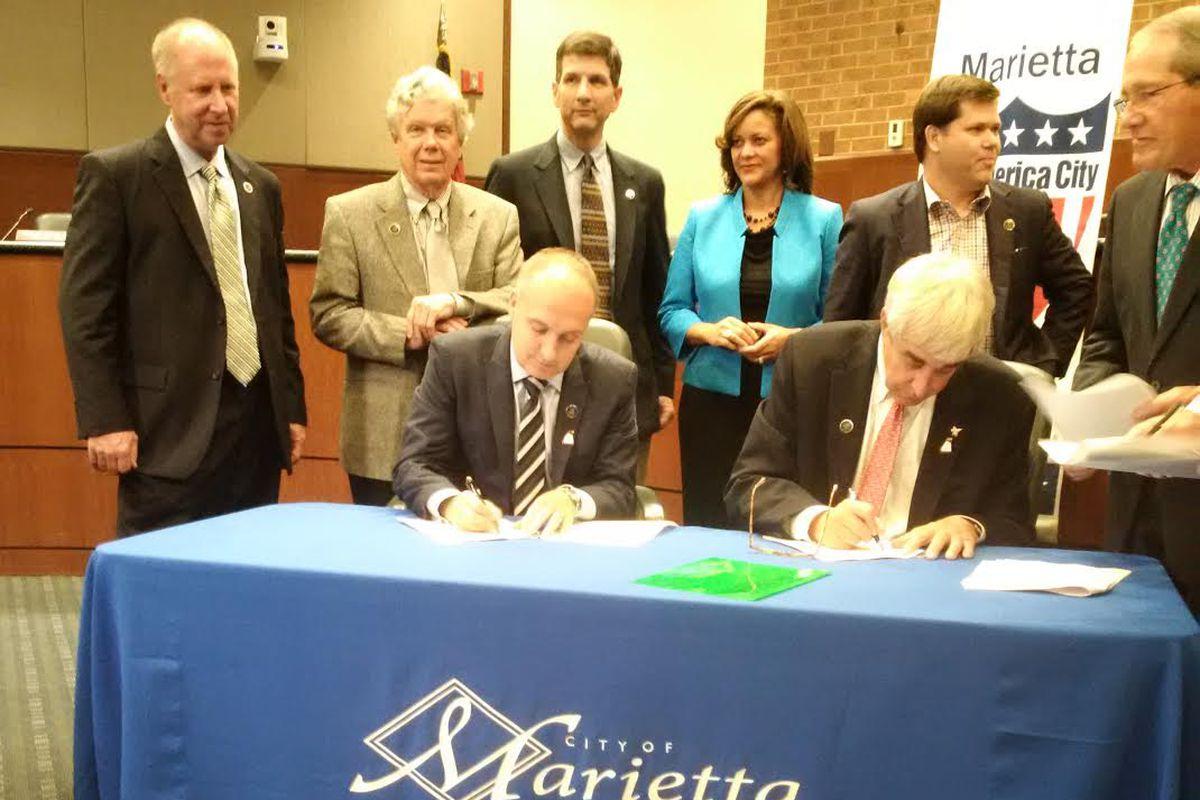 "AUFC President Darren Eales with Marietta Mayor Steve Tumlin. Both are signing the preliminary ""Memorandum of Understanding"" for the Marietta training facility."