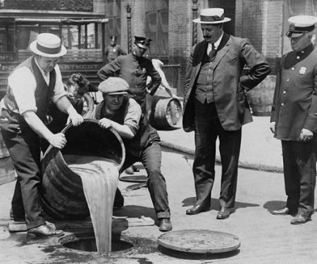 Workers pour out alcohol into the streets during Prohibition.