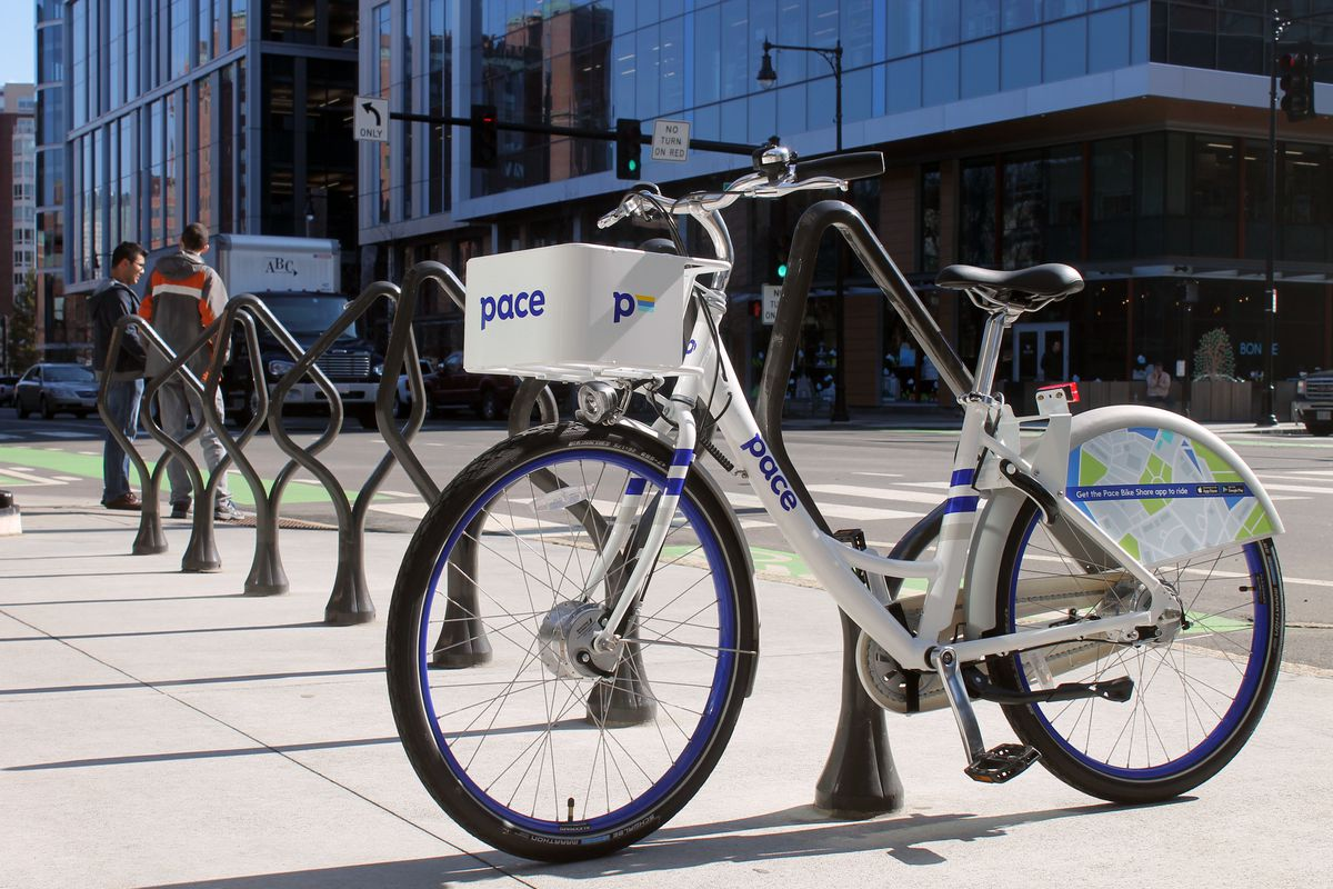 """White bike with white basket that reads """"Pace,"""" locked to a bike stand"""