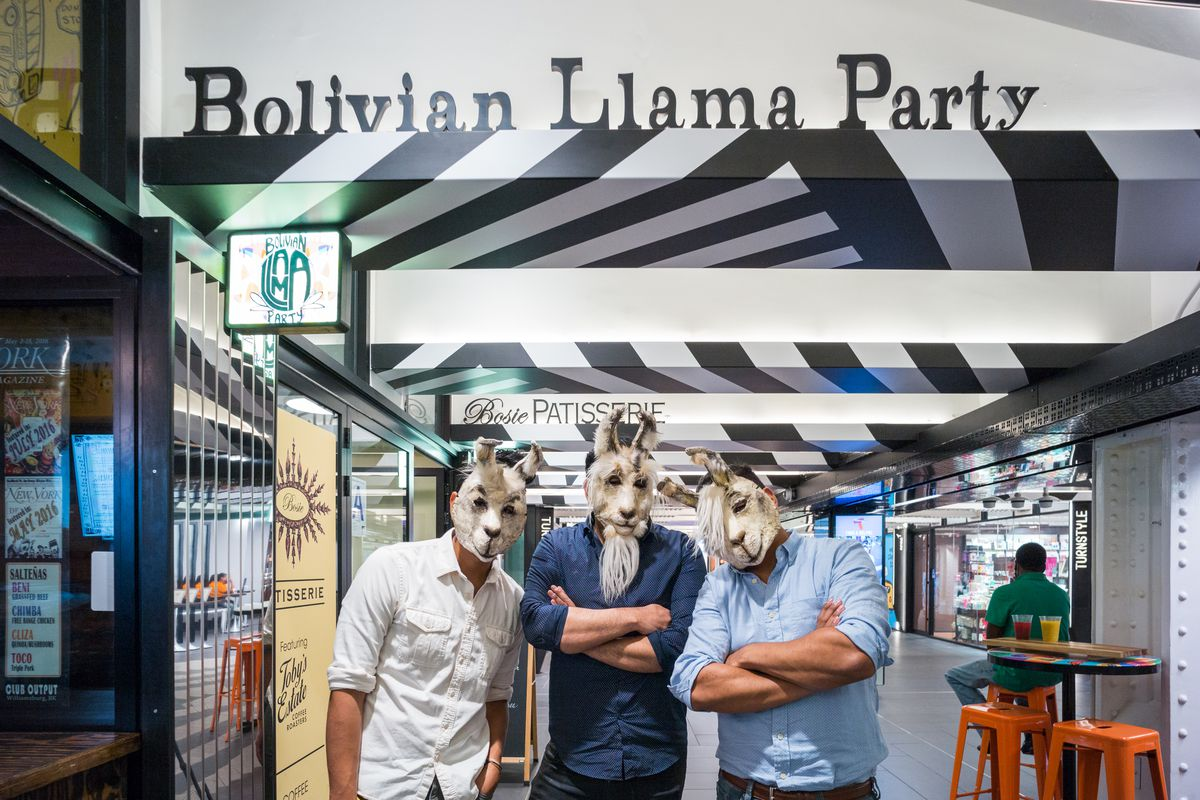 The three Oropeza brothers wear llama costume masks in front of Bolivian Llama Party at Turnstyle food hall in Manhattan