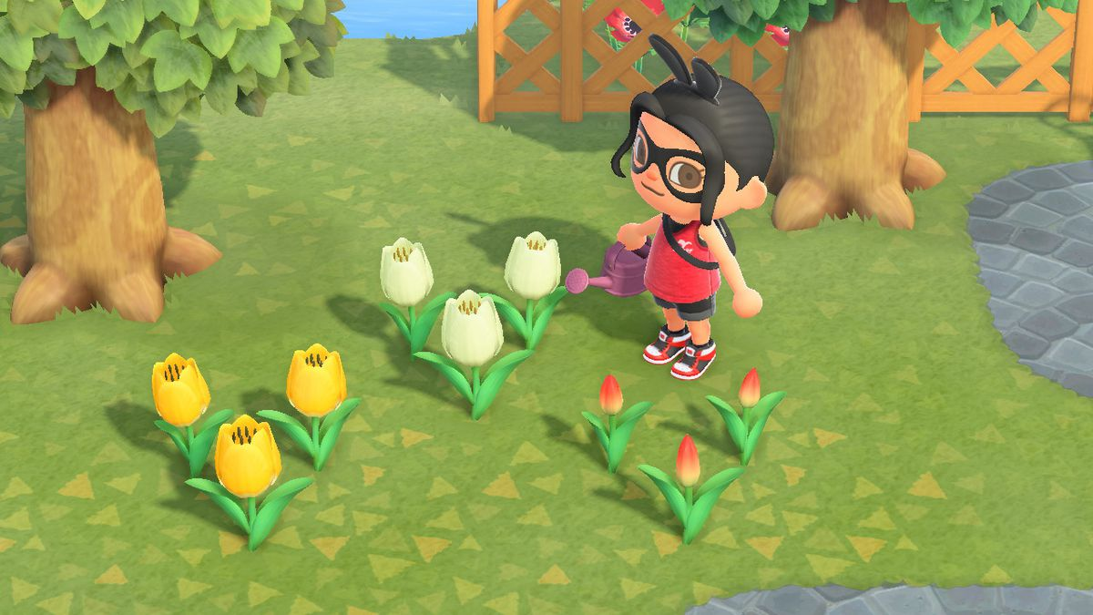 An Animal Crossing character stands near an array of tulips