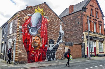 A new mural of Liverpool captain Jordan Henderson lifting the Premier League trophy and former captain Alan Hansen lifting the league trophy by artist Paul Curtis on the gable end of a house on Old Barn Road in Anfield, Liverpool.