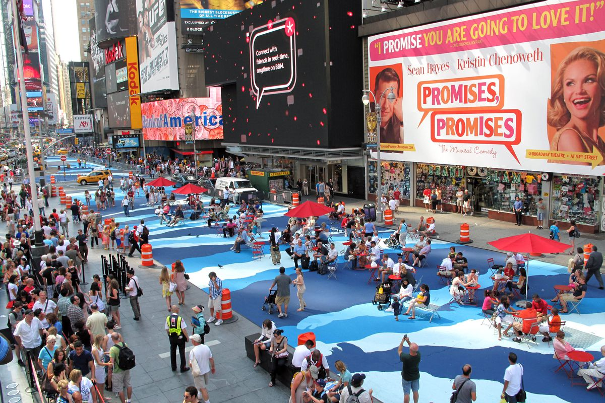 A busy New York City street hung with Broadway posters is painted with a rippling blue mural where people are sitting on beach chairs and under umbrellas.