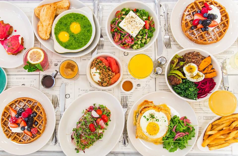 A spread of dishes including green shakshuka, fruit-topped waffle, salad with halloumi cheese, and fries