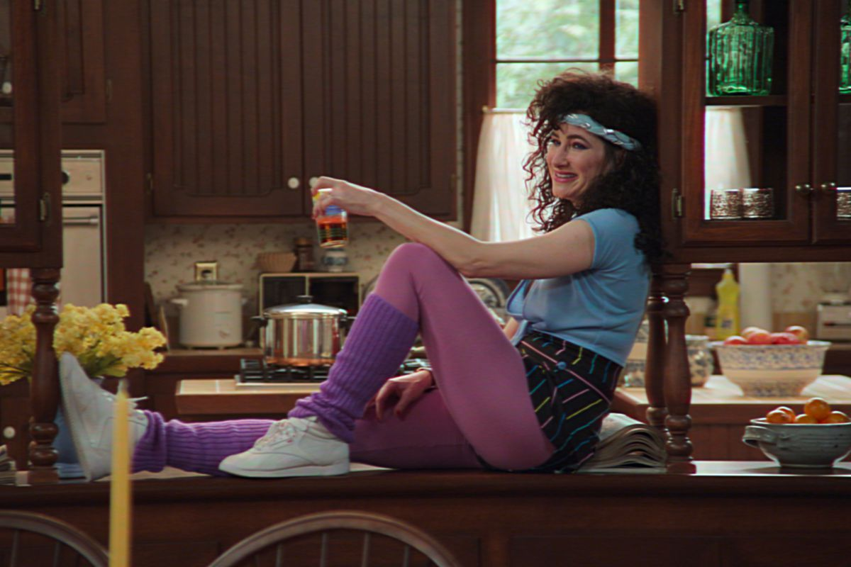Agnes, wearing '80s workout gear, sits on a countertop.