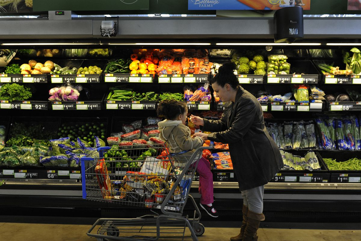 A person pushes a grocery cart containing a child past shelves of fresh vegetables in a supermarket.