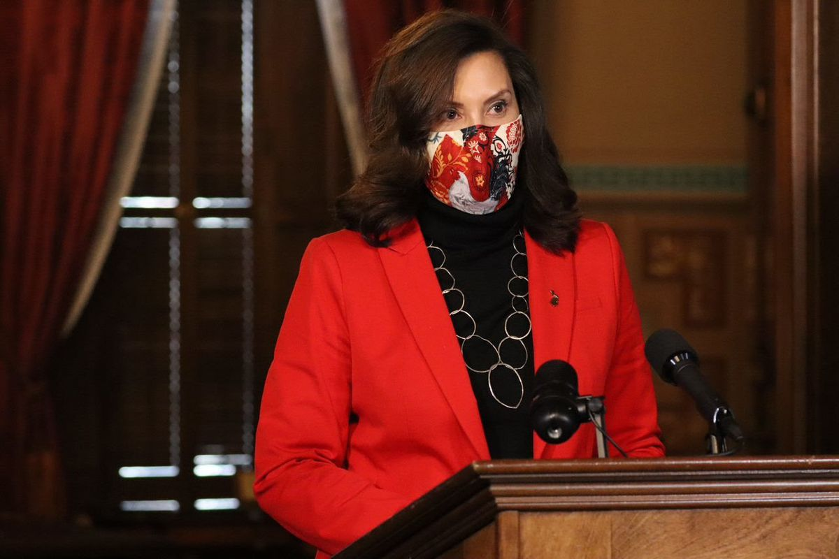 Michigan Gov. Gretchen Whitmer, wearing a mask and red jacket, stands at a podium