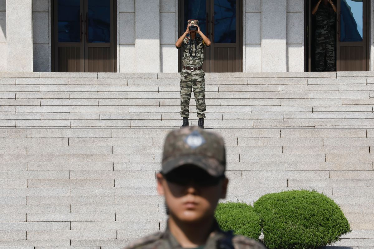 A soldier stands on stone steps with binoculars over his eyes. A second stands in front of him, closer to the camera, his hat low over his face.