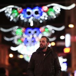 In this Tuesday, Jan 31, 2017 photo, Syrian Feras Zahka, 35, a Christian Orthodox from Damascus, who had fled to Turkey 3 years ago, walks in central Istanbul's Istiklal Avenue, the main shopping road of Istanbul. Zahka, has been preparing to emigrate to the U.S. since May of last year. He now says he was shocked when he heard U.S. President Donald Trump had suspended all refugee admissions to the U.S. for four months and banned the entry of Syrian refugees. Zahka is Christian and hopes his faith might be his only chance to settle in the U.S. finally. (AP Photo/Lefteris Pitarakis)