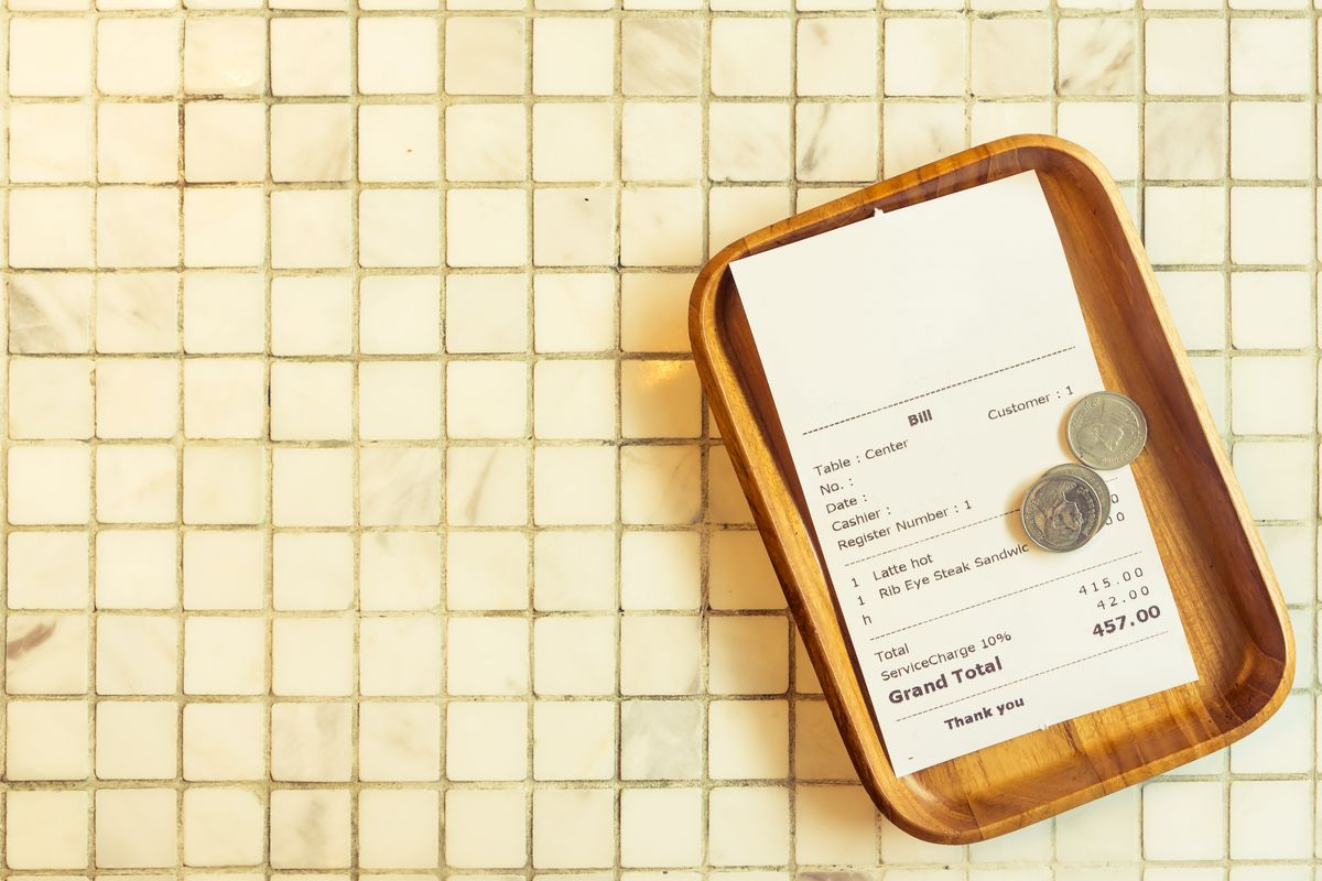small wooded tray with restaurant bill on off-white tile background