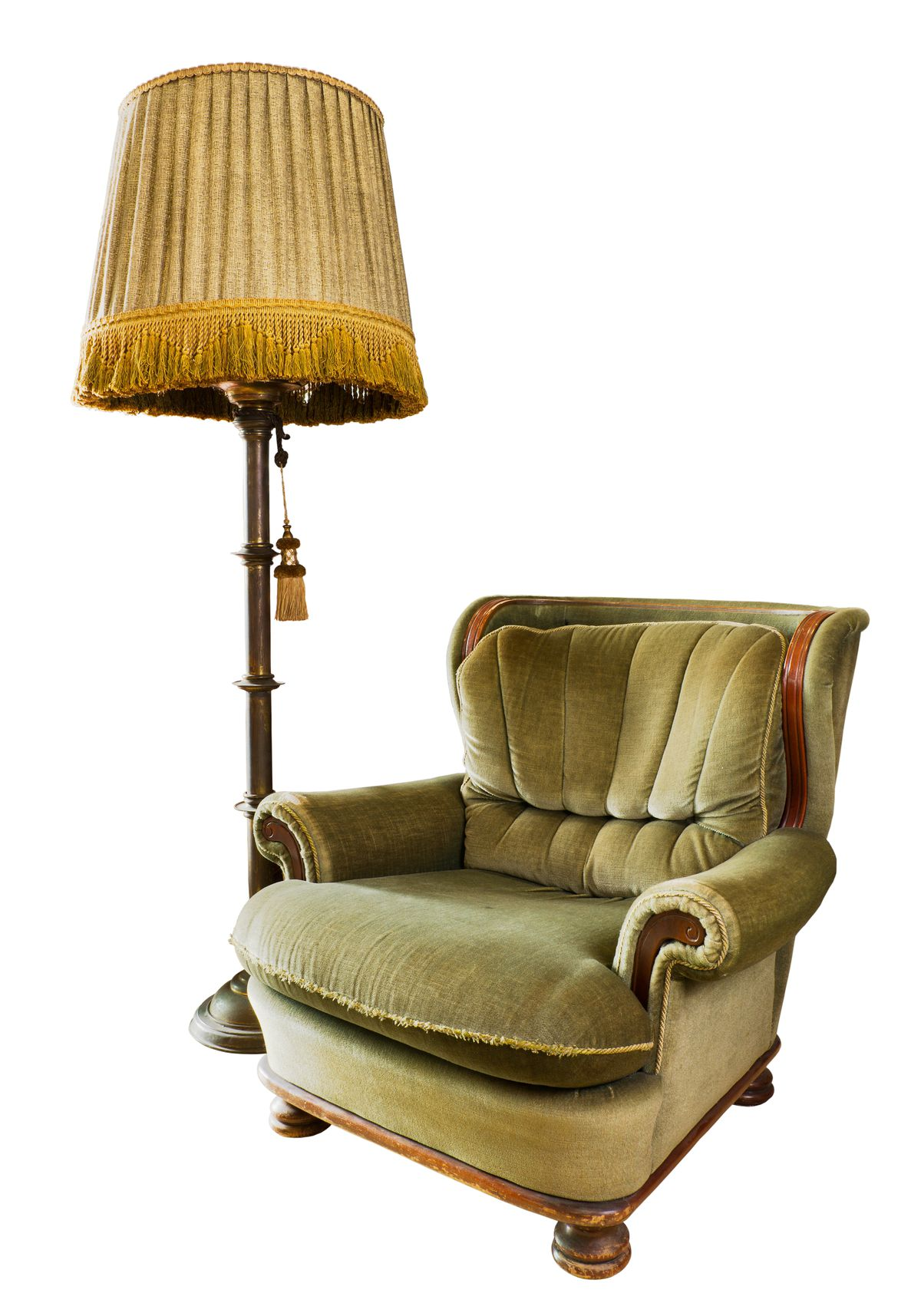 Cutout photo of an old upholstered armchair and a floor lamp with a large, fringed shade.