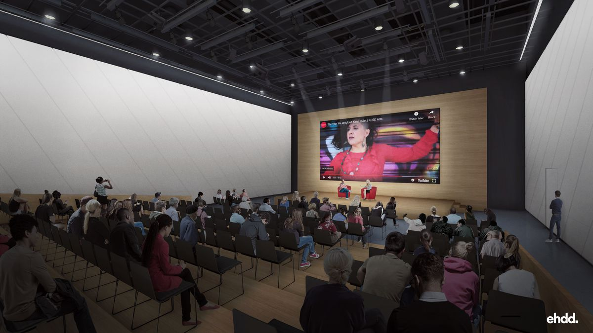 A theater-like common area with folding chairs set out and a YouTube video projected onto a screen.