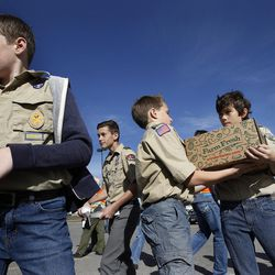 From left, Boy Scouts Evan Hofheins, Ashton Hofheins and Connor Troxel participate in a food drive assembly line in South Jordan on Saturday, March 21, 2015.