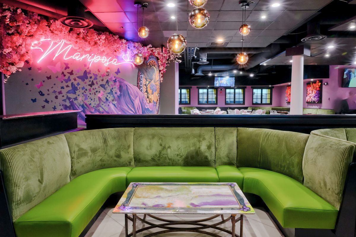 A lounge with a green couch and neon sign