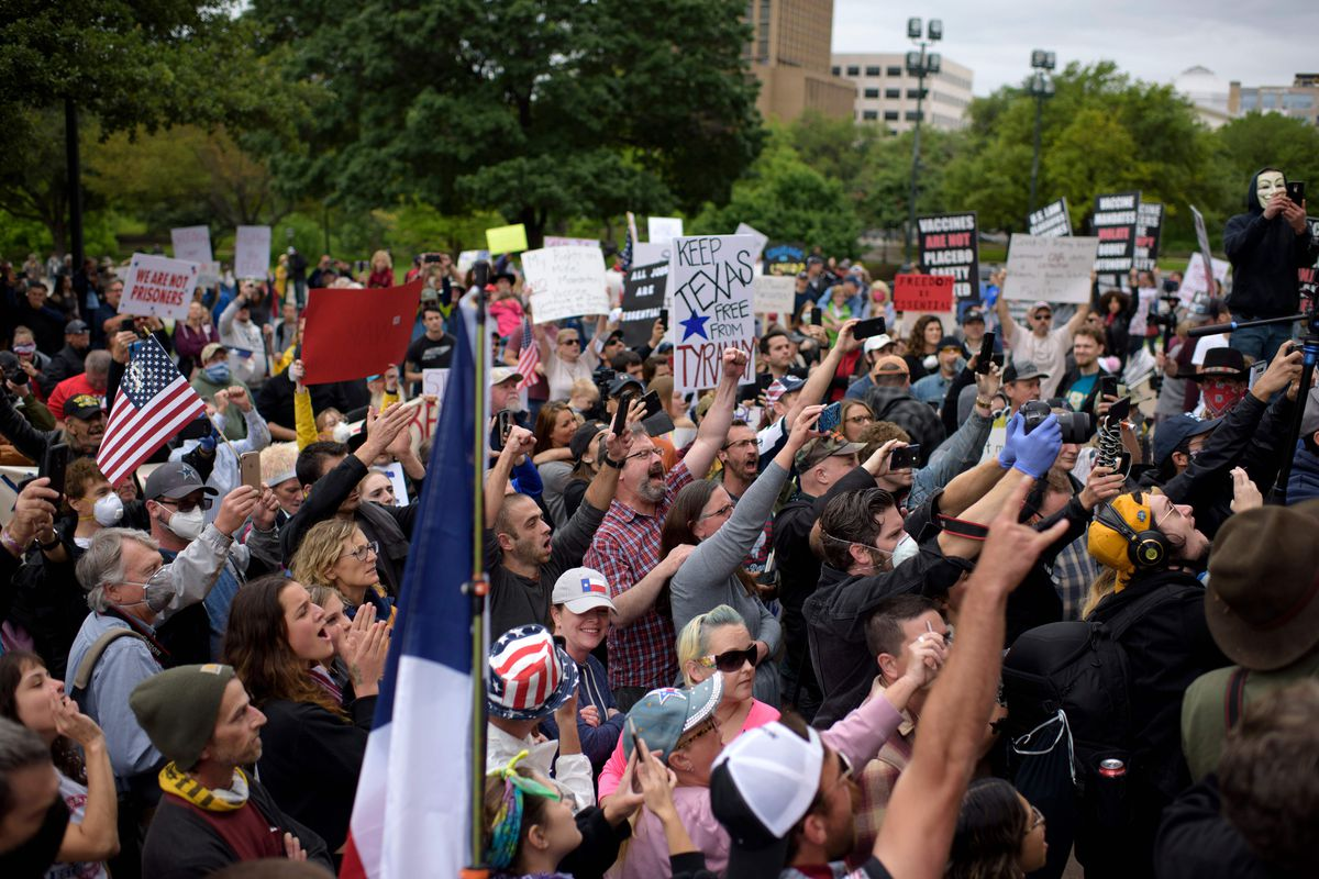 Hundreds of people, many carrying Texas flags and homemade signs, raises their arms as they chant. Few are wearing masks or gloves.