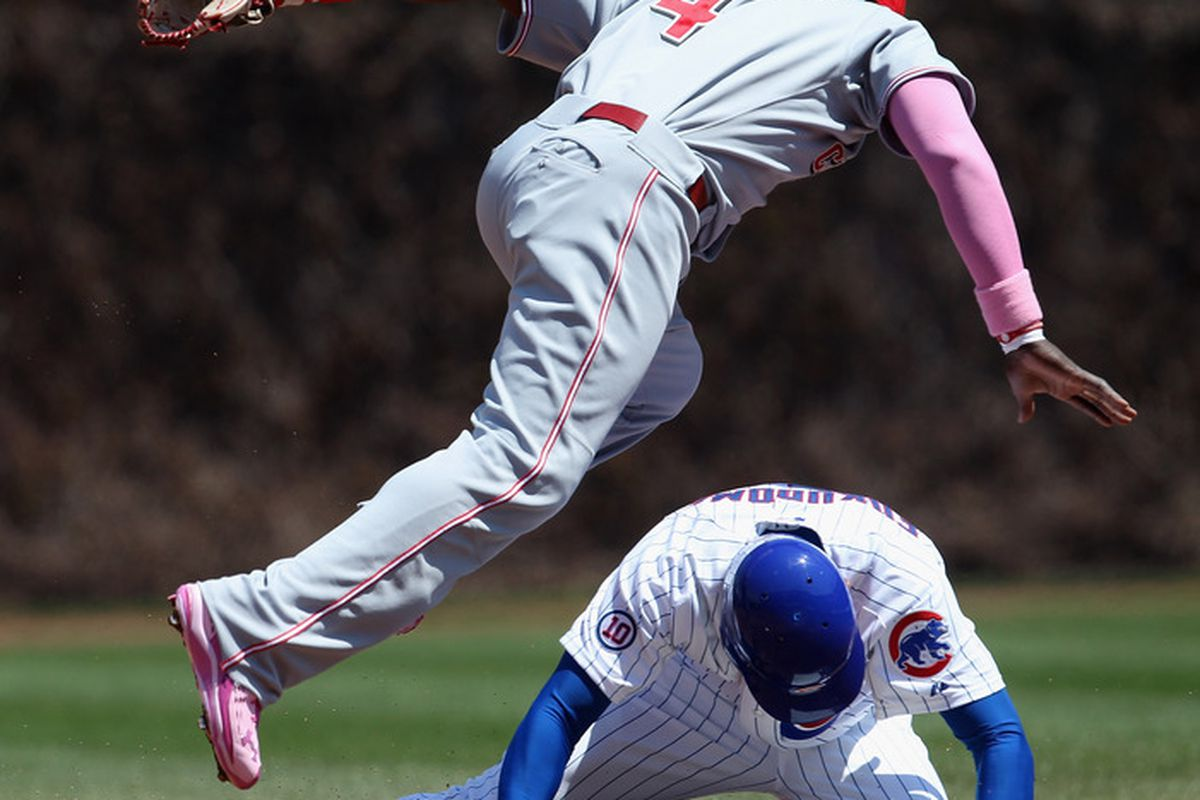 Brandon Phillips of the Cincinnati Reds hops over Kusuke Fukudome of the Chicago Cubs after making a double play throw   at Wrigley Field on May 8, 2011 in Chicago, Illinois. The Reds defeated the Cubs 2-0. (Photo by Jonathan Daniel/Getty Images)