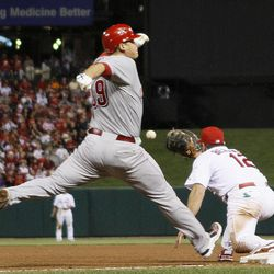 Cincinnati Reds' Devin Mesoraco reaches safely ahead of the throw to St. Louis Cardinals first baseman Lance Berkman on an RBI-single in the fifth inning during a baseball game, Wednesday, April 18, 2012, in St. Louis. The Cardinals won 11-1.