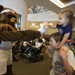 Jazz Bear gives a teddy bear donated by Canopies for Kids to Bryten Munoz and her brother Jaycen at Shriners Hospitals for Children in Salt Lake City on Thursday, Sept. 14, 2017.