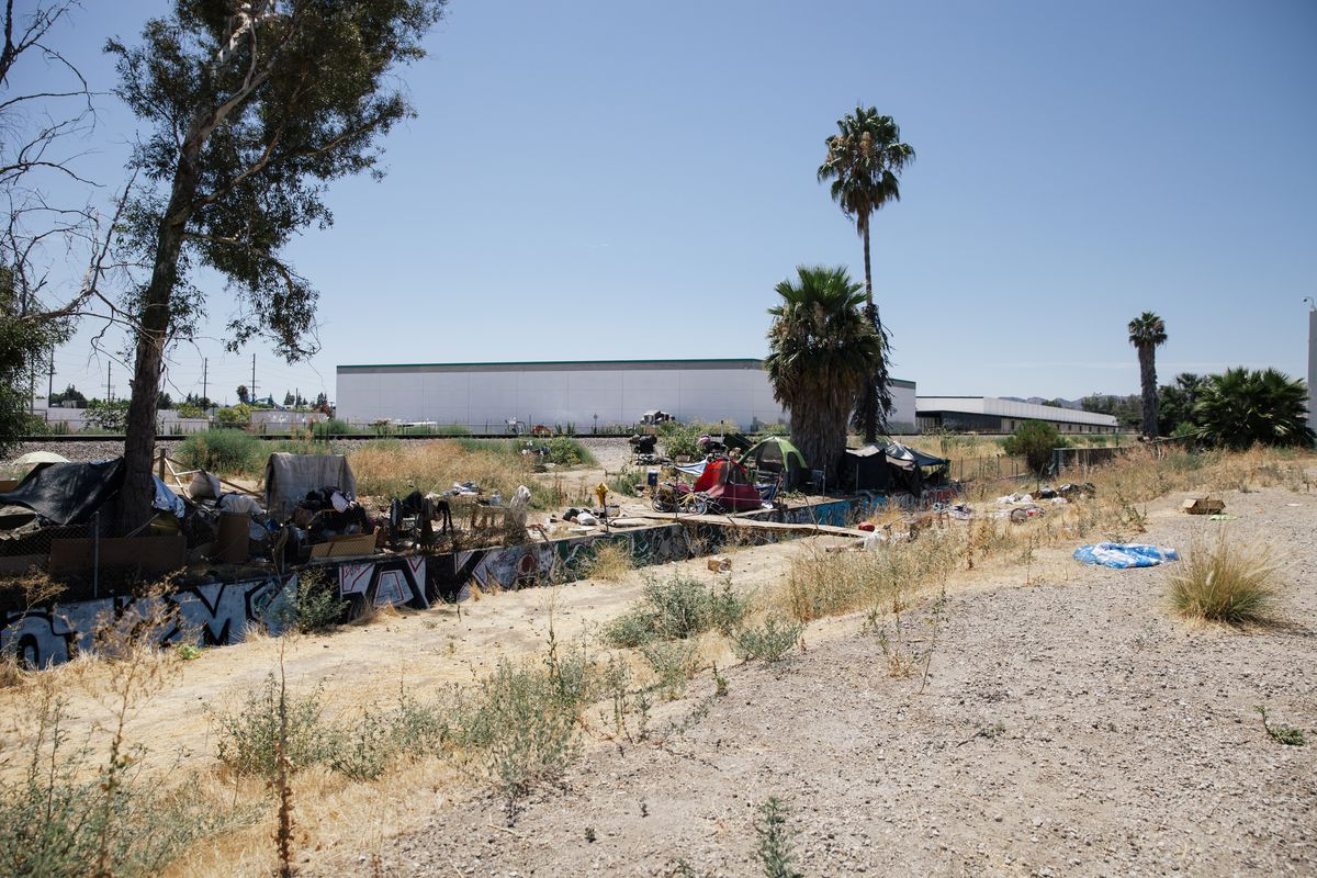 A dusty landscape with a low retaining wall covered in graffiti. Behind it, a homeless encampment.