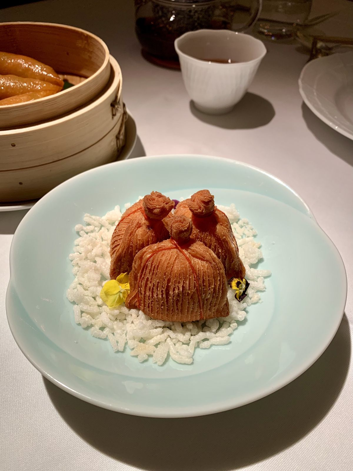 three times King crab puff at Park Chinois on rice on a pale blue plate with mood lighting