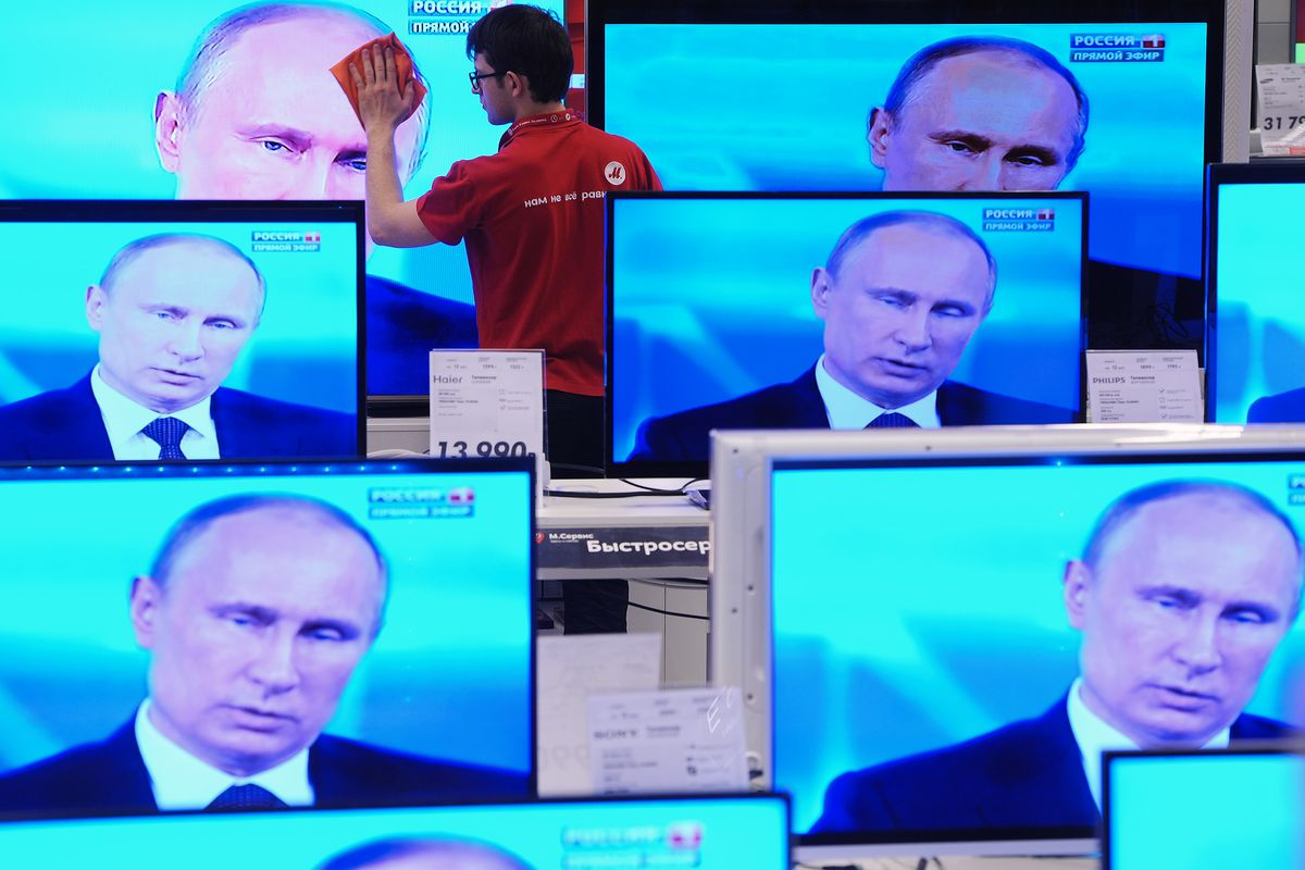 A shop assistant cleans a TV screen during Russian President Vladimir Putin's nationally televised Q&A session in a shop on April 17, 2014, in Moscow, Russia.