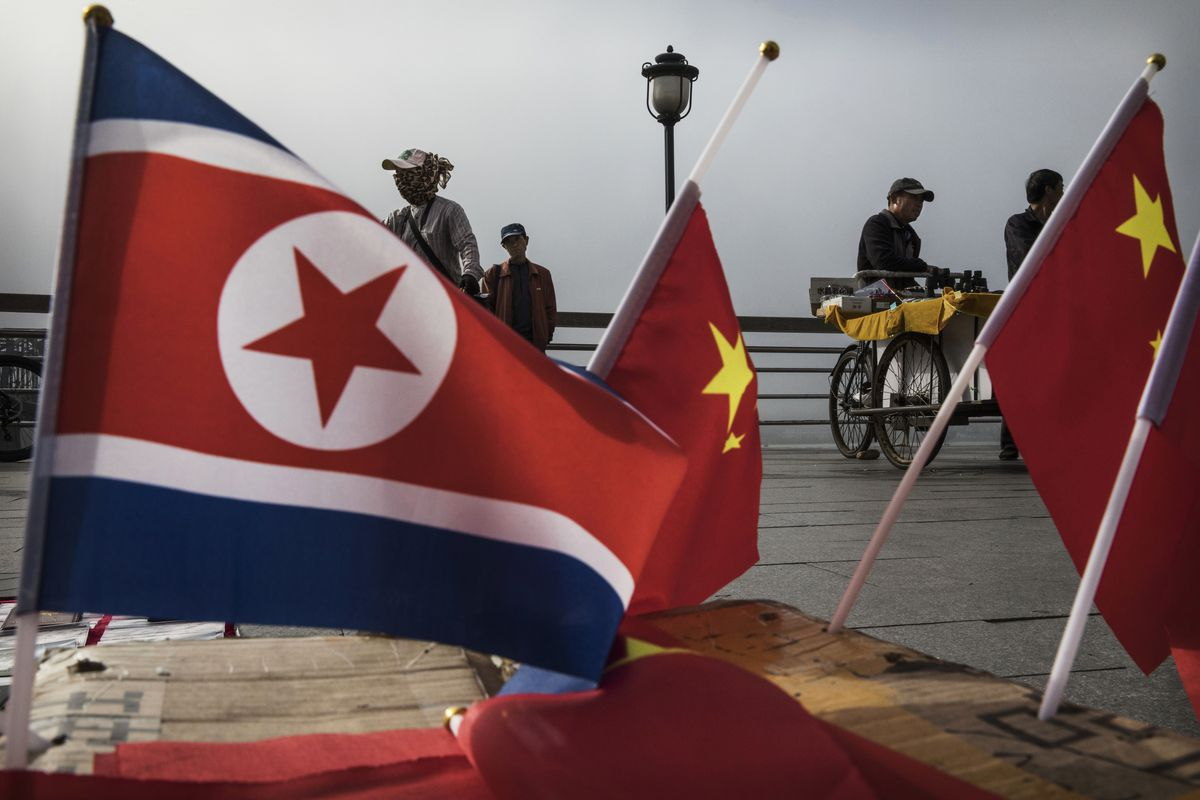 North Korean and Chinese flags on display on a boardwalk.